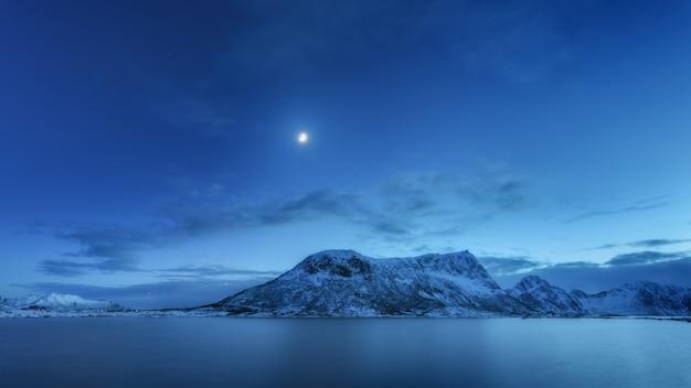 Montanhas cobertas de neve contra o céu azul com nuvens e lua no inverno à noite Foto Premium