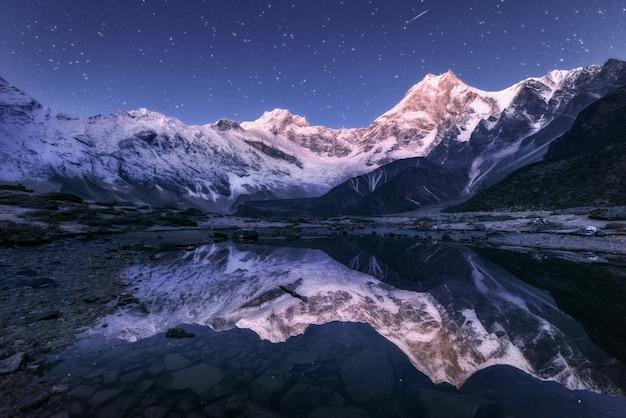 Montanhas do himalaia e lago de montanha à noite estrelada no nepal Foto Premium
