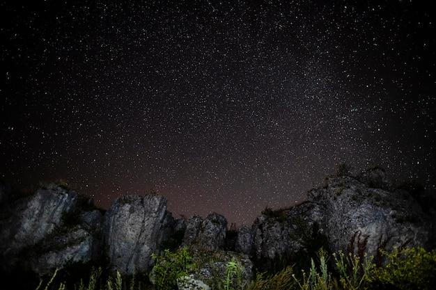 Montanhas rochosas e céu estrelado Foto gratuita