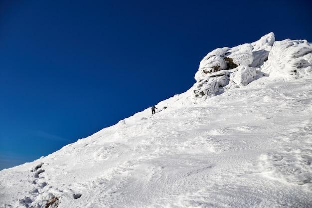 Montanhista de homem caminhando na colina coberta de neve fresca. montanhas carpathian Foto Premium
