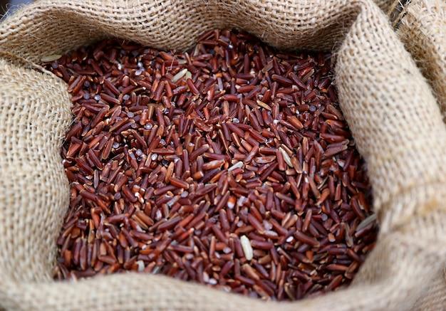 Montão de arroz de arroz de cor roxo profundo cru em um saco de cânhamo natural Foto Premium
