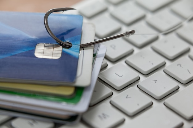 Monte de cartões de crédito no gancho de pesca no laptop Foto Premium