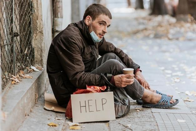 Morador de rua ao ar livre com sinal de ajuda e copo Foto gratuita
