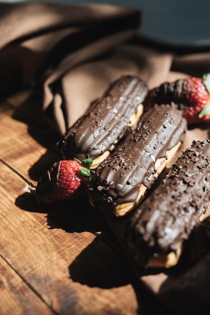 Morango com chocolate éclairs na mesa de madeira na luz solar Foto gratuita