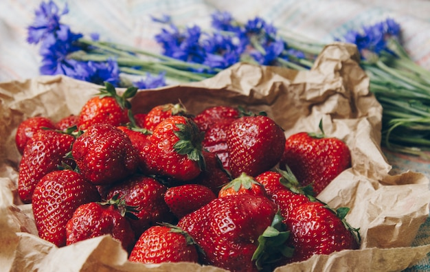 Morango madura com flores em papel envoltório close-up. trawberries maduros frescos. Foto Premium