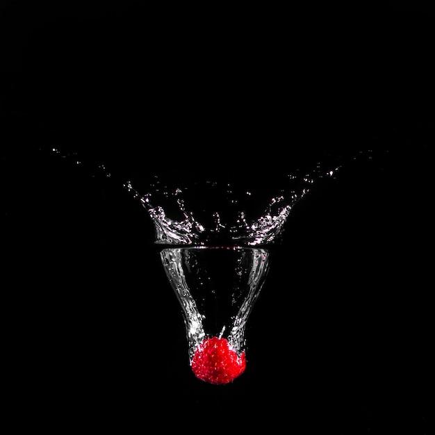 Morango mergulhando na água Foto gratuita