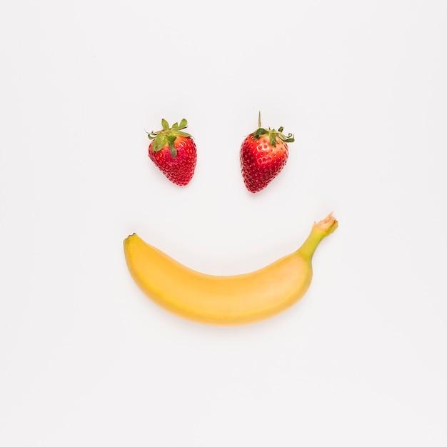 Morango vermelha e banana amarela no fundo branco Foto gratuita
