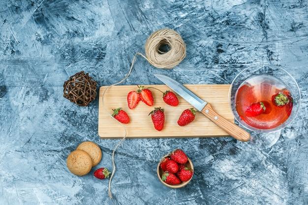 Morangos de close-up e uma faca na tábua com um copo de coquetel, clew, uma tigela de morangos e biscoitos em fundo de mármore azul e cinza escuro. espaço livre horizontal para o seu texto Foto gratuita