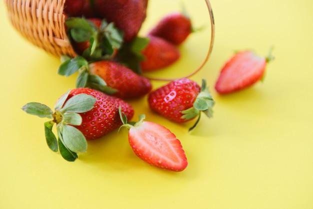 Morangos frescas no fundo amarelo. colheita de morango vermelha madura na cesta Foto Premium