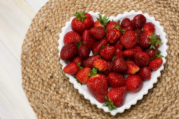 Morangos fresco maduras servidas em uma placa branca do coração com um jack clothtable Foto Premium