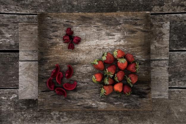 Morangos frescos e pétalas de flores vermelhas em uma superfície de madeira Foto gratuita