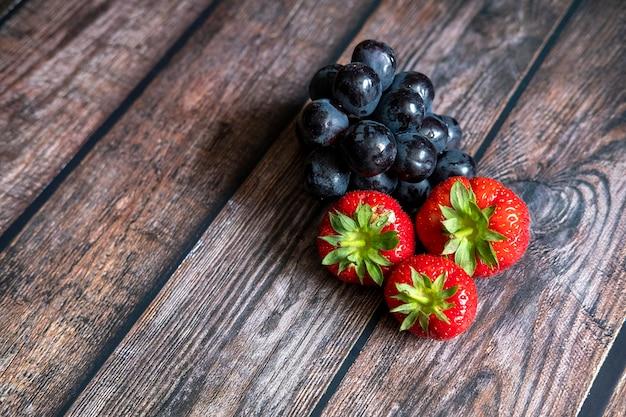 Morangos frescos escoceses e uvas pretas em cima da mesa de madeira. Foto gratuita