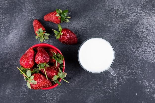 Morangos leigos planos na tigela e outros ao redor com um copo de leite na mesa escura Foto gratuita