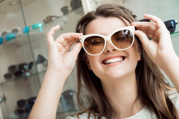 Morena atraente alegre escolhendo novo par de óculos de sol com a ajuda do assistente de loja Foto gratuita