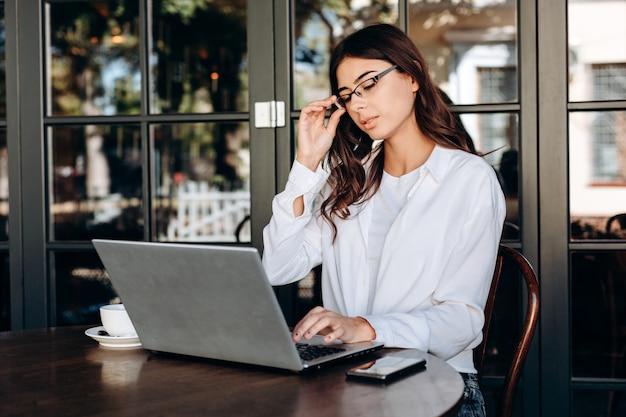 Morena atraente em copos trabalhando no laptop em novo projeto Foto Premium