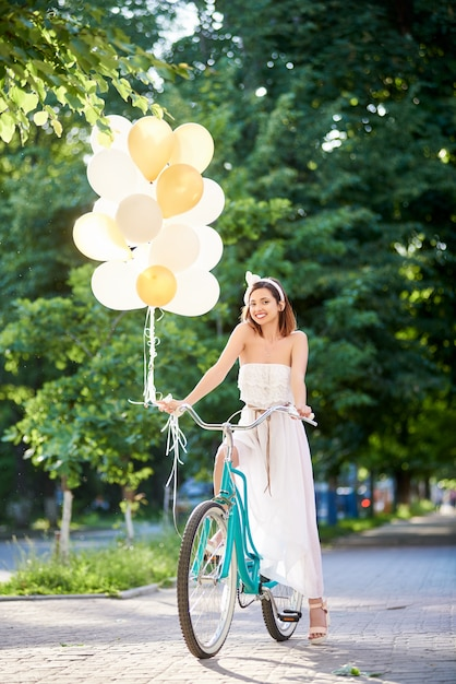 Morena atrativa de sorriso que guarda ballons ao conduzir a bicicleta azul na aleia do parque. Foto Premium