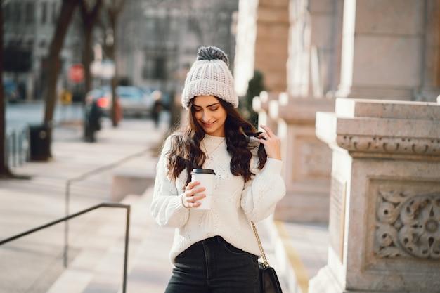 Morena bonita em uma camisola branca em uma cidade Foto gratuita