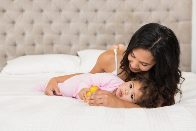 Morena brincando com seu bebê e um pato na cama Foto Premium