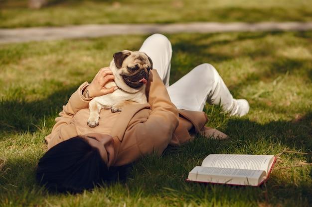 Morena com um casaco marrom caminha com pug Foto gratuita