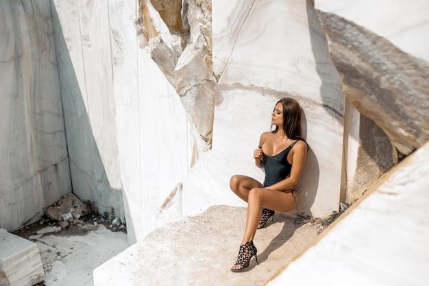 Morena encantadora, vestida com um maiô preto e sapatos de salto alto, posando em pedras brancas Foto Premium