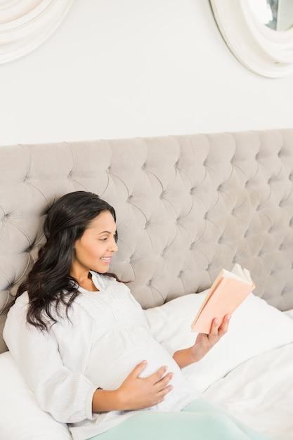 Morena grávida, lendo um livro na cama Foto Premium