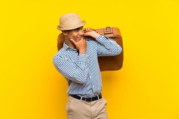 Morena homem segurando uma mala vintage, olhando de lado Foto Premium