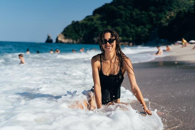 Morena jovem sexy, posando de joelhos no mar Foto gratuita