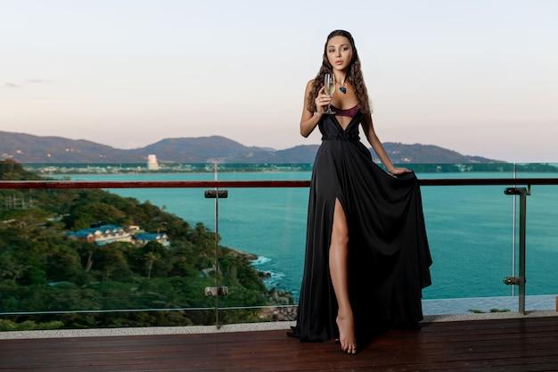 Morena luxuosa posando em um vestido longo preto em jóias caras com um copo de varanda de vinho. vistas luxuosas da ilha tropical e do mar Foto Premium