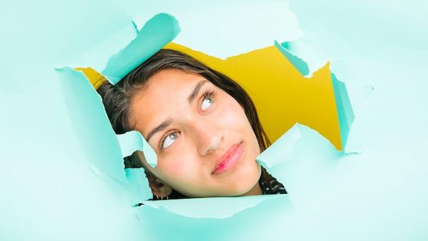 Morena modelo posando através do buraco de papel Foto gratuita