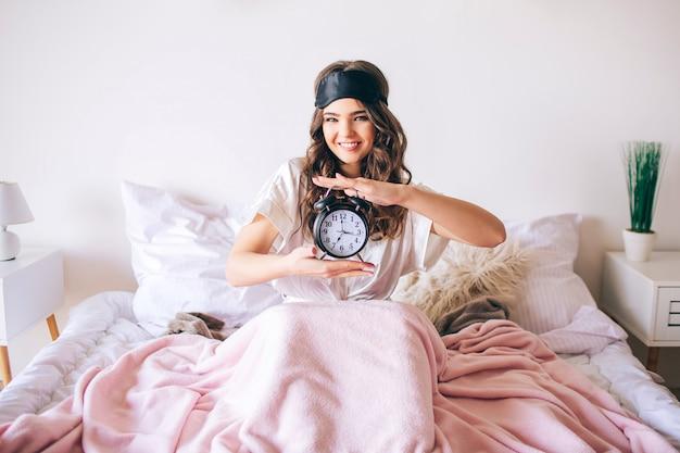 Morena morena bonita jovem acorda em sua cama. alegre mulher legal segurando o relógio nas mãos e sorrir. olhe diretamente para a câmera. máscara para dormir na testa. modelo feliz positivo no quarto. Foto Premium