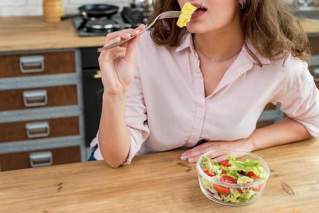 Morena mulher comendo uma salada Foto gratuita
