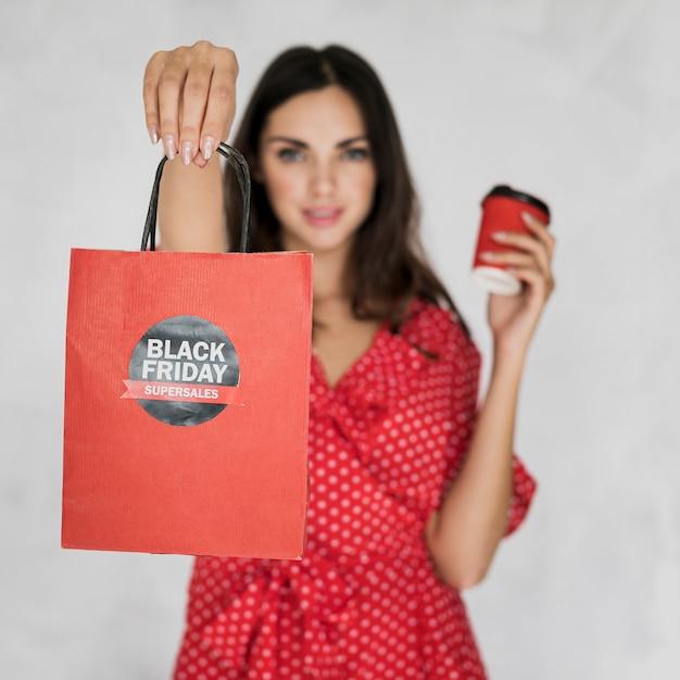 Morena mulher segurando o saco de compras preto sexta-feira Foto gratuita