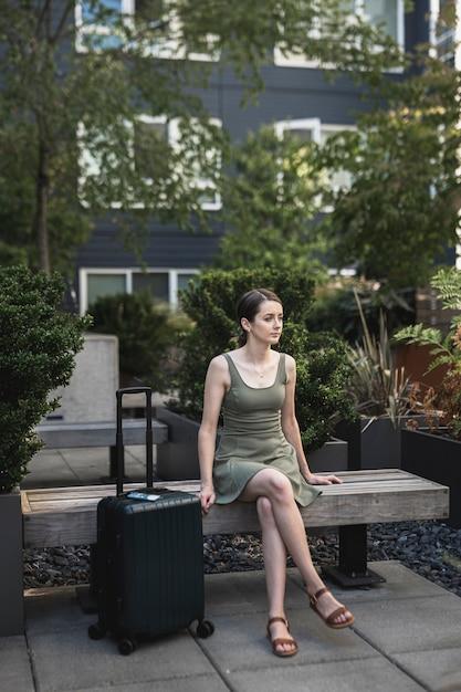 Morena mulher sentada no assento de cimento com uma mala Foto gratuita