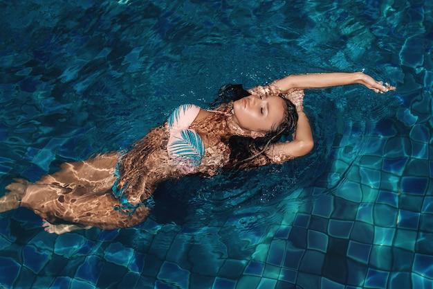 Morena sexy, posando na piscina com os olhos fechados Foto Premium