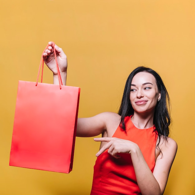 Morena sorridente, mostrando o saco de compras Foto gratuita
