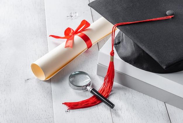 Mortarboard, lupa e diploma amarrado com fita vermelha na mesa de madeira branca Foto Premium