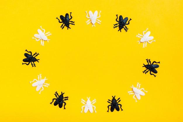 Moscas de plástico brancas e pretas mentem em um círculo sobre um fundo de papelão moldura amarela. convite de halloween pronto. copie o espaço Foto Premium