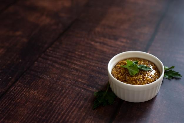 Mostarda no sortido: mostarda de dijon, mostarda russa em chamas e grãos secos em taças Foto Premium