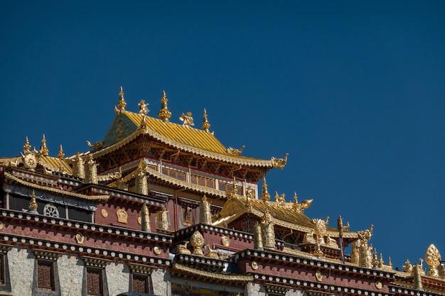 Mosteiro de ganden sumtseling (mosteiro de songzanlin) com lago e céu azul claro, shangri-la, china Foto Premium
