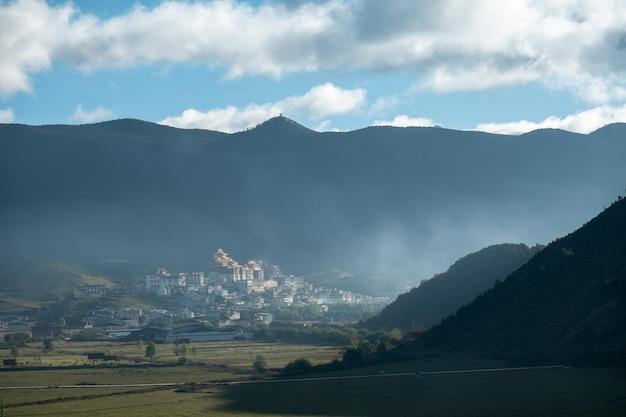 Mosteiro de ganden sumtseling na névoa da manhã Foto Premium