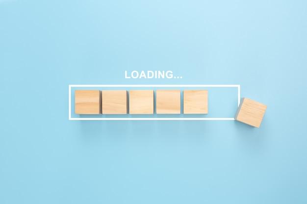 Mostrando a barra de carregamento com cubo de madeira sobre fundo azul. blocos de madeira com a palavra loading no progresso da barra de carregamento. Foto Premium