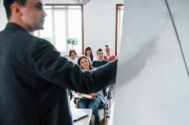 Mostrando dados. grupo de pessoas em conferência de negócios em sala de aula moderna durante o dia Foto gratuita