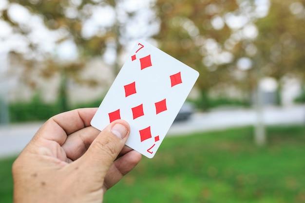 Mostrando uma carta de baralho na mão Foto Premium