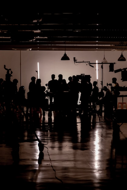 Mostre em silhueta imagens da produção de vídeo nos bastidores, equipe lightman e cameraman trabalhando em conjunto com o diretor no estúdio Foto Premium