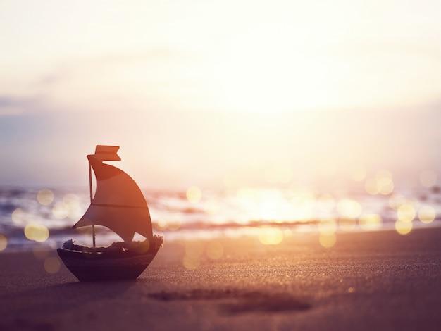 Mostre em silhueta o brinquedo do bote na areia na praia do por do sol. Foto Premium