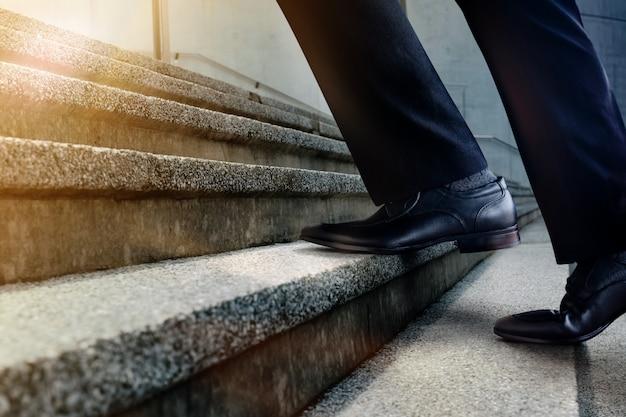 Motivação e conceito desafiador de carreira. passos para o sucesso. seção baixa do empresário andando na escadaria. macho em vestido formal preto Foto Premium