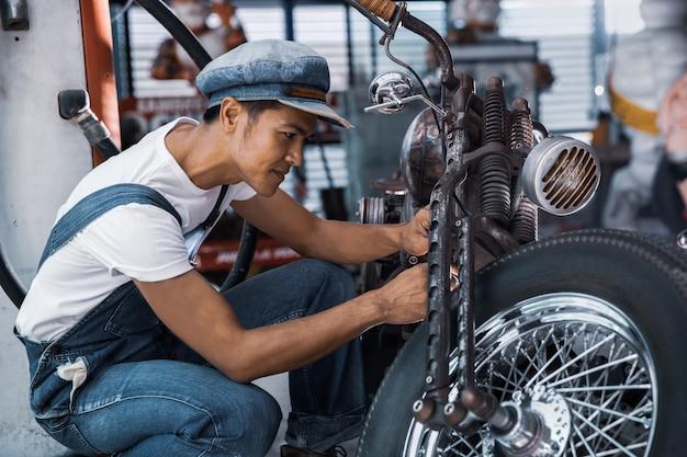 Moto mecânico de reparação técnico na oficina Foto Premium