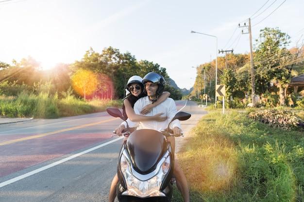 Motocicleta de equitação de casal feliz no campo excited mulher e homem viajam na viagem de moto Foto Premium