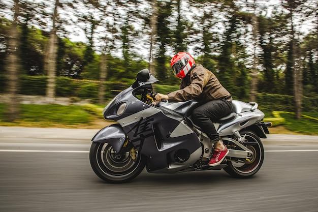 Motociclismo de alta velocidade na estrada em frente à floresta Foto gratuita