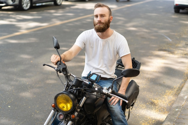 Motociclista bonita pensativa posando com moto Foto gratuita